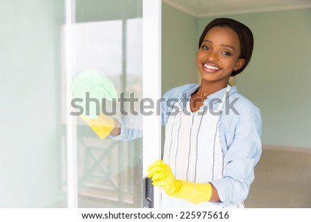portrait of african housewife cleaning a door glass