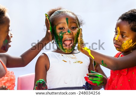 Portrait of African kids painting themselves with color paint.Isolated against light background. - stock photo