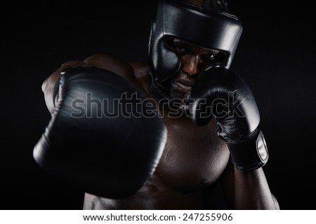 Portrait of african male practicing boxing looking at camera against black background. Male boxer throwing a punch in front. Young sportsman training boxing. - stock photo