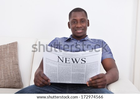Portrait Of African Man Sitting On Sofa With Newspaper - stock photo