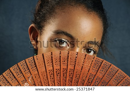 Portrait of african teen girl covering her face with fan - stock photo