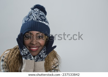 Portrait of african woman on gray background wearing woolen accessories - stock photo