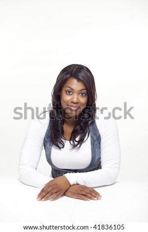 portrait of African woman smiling with hands crossed - stock photo