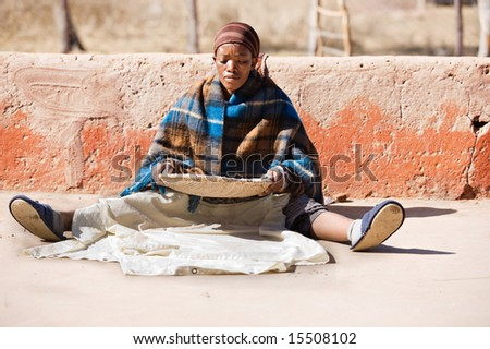 Portrait of African woman with a basket of sorghum, staple food in africa - stock photo