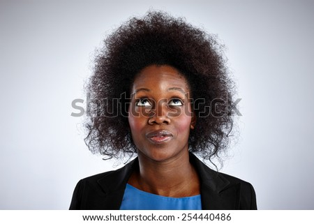 Portrait of african woman with curly hair looking up against white background - stock photo