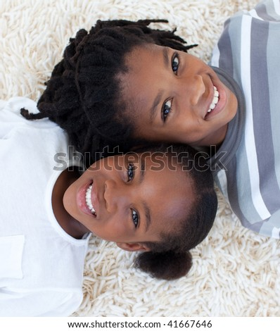 Portrait of Afro-American brother and sister on floor with heads together - stock photo