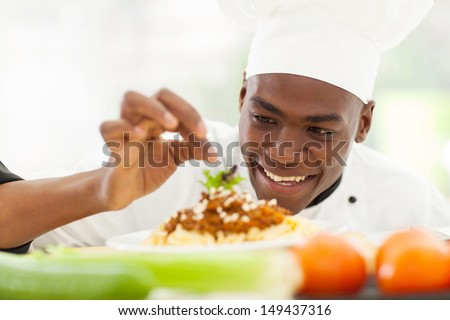 portrait of Afro American chef in restaurant kitchen garnishing pasta dish - stock photo