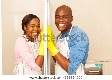 portrait of afro american couple cleaning bathroom