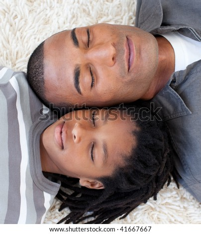 Portrait of Afro-American father and son sleeping on the floor at home - stock photo