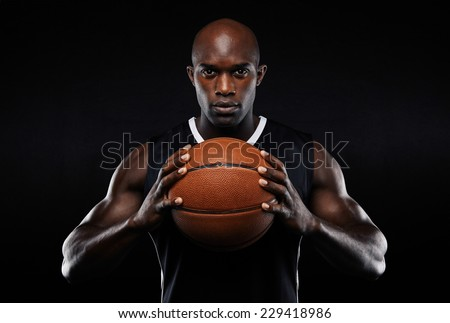 Portrait of afro american male basketball player with a ball over black background. Fit young man in sportswear holding basketball. - stock photo