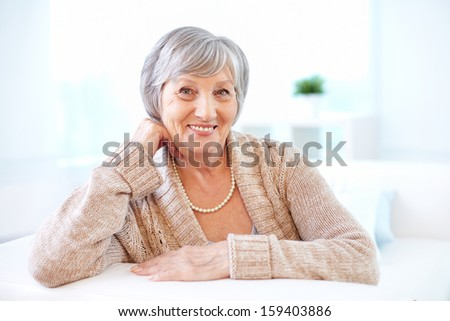 Portrait of aged female looking at camera with smile - stock photo
