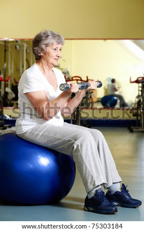 Portrait of aged woman doing physical exercise with barbells while sitting on blue ball - stock photo