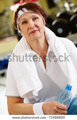 Portrait of aged woman with bottle of water in hand - stock photo