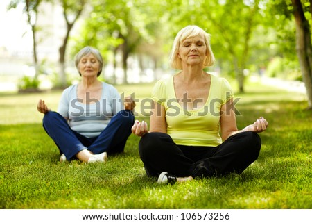 Portrait of aged women doing yoga exercise - stock photo