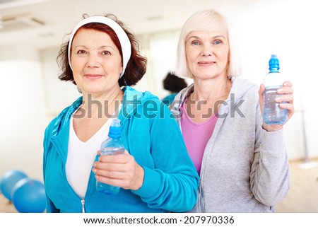 Portrait of aged women with plastic bottles looking at camera - stock photo