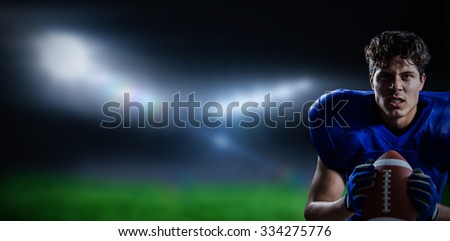 Portrait of aggressive American football player against football pitch under bright lights - stock photo