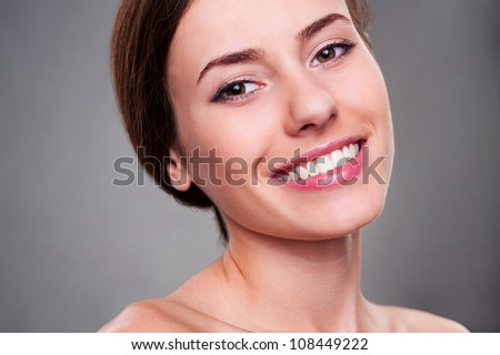 portrait of alluring young woman smiling and looking at camera over grey background - stock photo