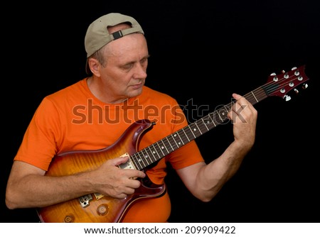 Portrait of amateur musician playing guitar - stock photo