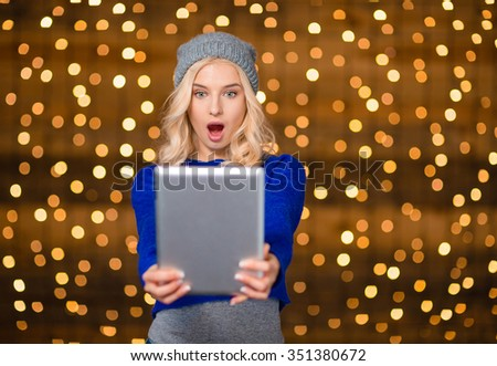 Portrait of amazed blonde woman using tablet computer over holiday lights on background - stock photo