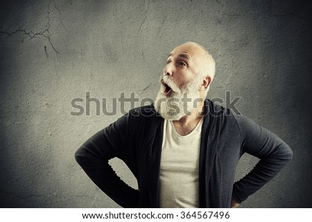 portrait of amazed screaming man with empty copyspace for your text over grey wall