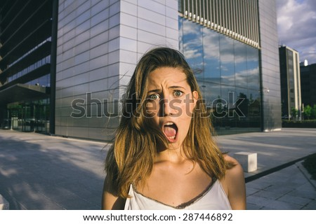 Portrait of amazed woman in a city - stock photo
