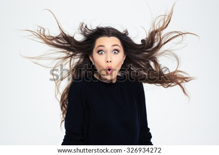 Portrait of amazed young girl looking at camera isolated on a white bakground - stock photo