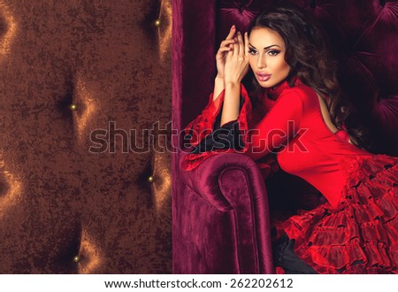 Portrait of amazing beautiful sexy brunette woman with lovely plump lips in red tango dress posing sitting in a velvety armchair and dreaming. Dark brown luxury velvet background with copyspace