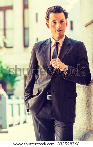 Portrait of American Businessman. Dressing formally in suit, necktie, wristwatch, a young man standing against wall outside office building on street, looking away, thinking. Instagram filtered look.