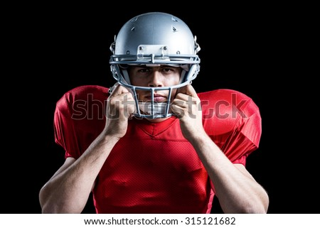 Portrait of American football player holding helmet while playing against black background