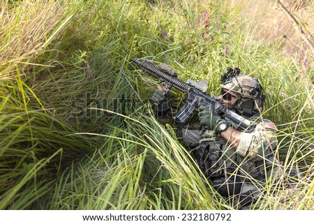 Portrait of American Soldier aiming his rifle on the grass - stock photo