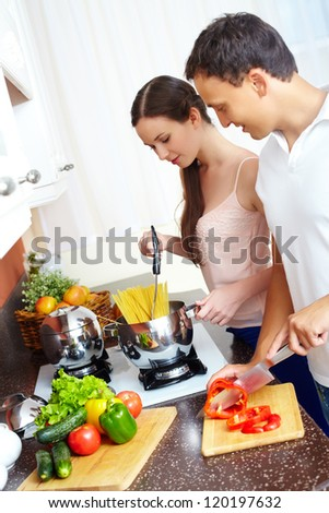 Portrait of amorous couple cooking pasta in the kitchen