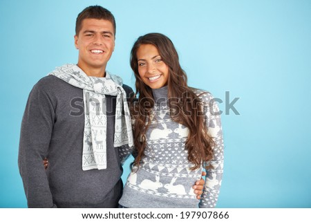 Portrait of amorous couple in fashionable pullovers looking at camera with smiles - stock photo