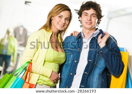 Portrait of amorous couple looking at camera with smiles after great shopping - stock photo