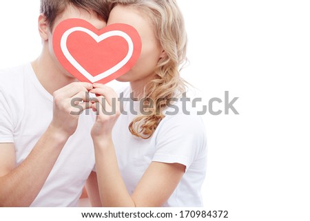 Portrait of amorous young couple holding red heart by their faces - stock photo