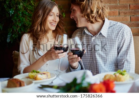 Portrait of amorous young couple toasting with red wine - stock photo