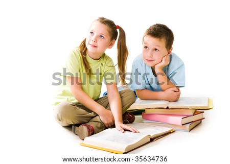 Portrait of amused pupils looking aside during reading books - stock photo