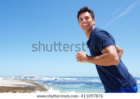 Portrait of an active man casually running at the beach  - stock photo