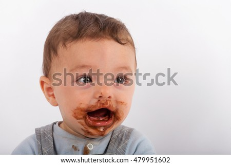 Portrait of an adorable baby boy after eating a plate of chocolate