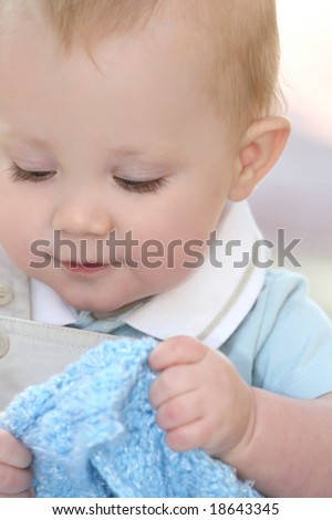 Portrait of an adorable baby boy holding a blue blanket - stock photo