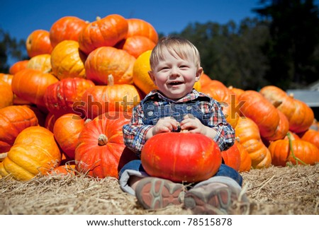 Portrait of an adorable baby boy with a pumpkin - stock photo