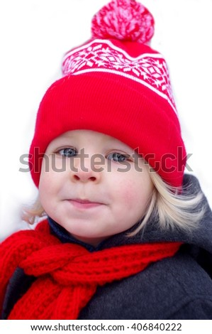 Portrait of an adorable baby boy with big blue eyes wearing a knit red and red winter hat - stock photo