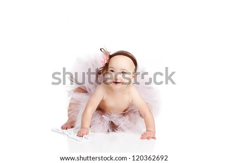Portrait of an adorable baby girl dressed in a pink and brown tutu and headband.  Isolated on white.
