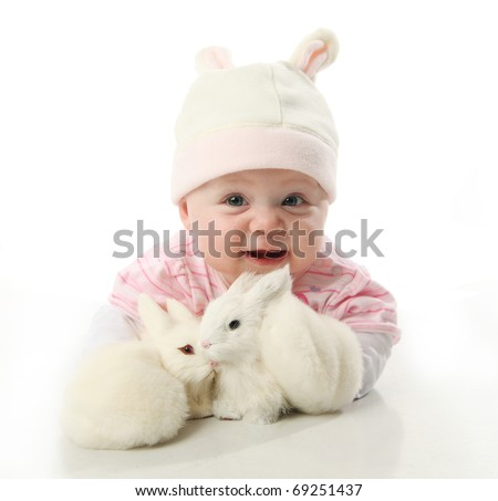 Portrait of an adorable baby girl wearing a bunny rabbit costume and petting two baby bunnies - stock photo