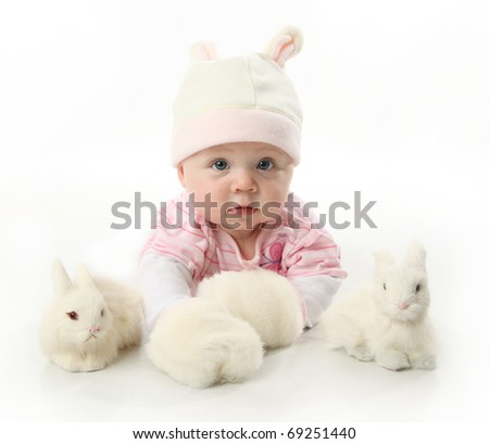 Portrait of an adorable baby girl wearing a bunny rabbit costume and petting two white bunnies - stock photo