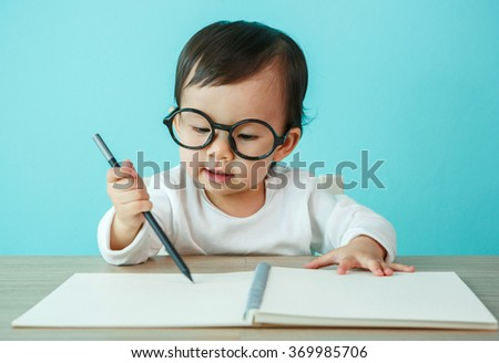 Portrait of an adorable baby girl wearing glasses on the table (soft focus on the eyes)