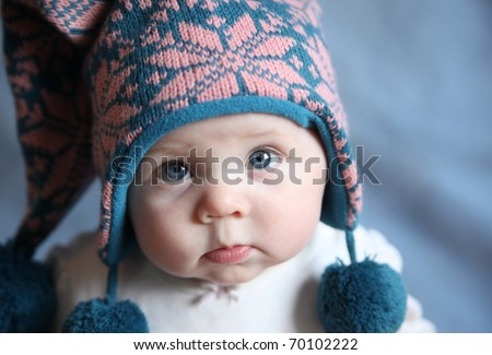 Portrait of an adorable baby girl with big blue eyes wearing a knit pink and blue winter hat - stock photo