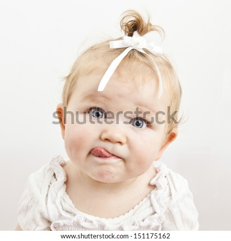 Portrait of an adorable baby girl with tongue sticking out - stock photo