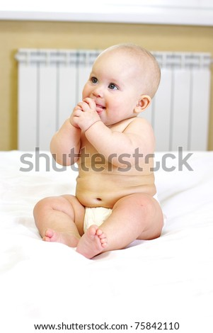 Portrait of an adorable baby sitting up wearing a diaper and smiling