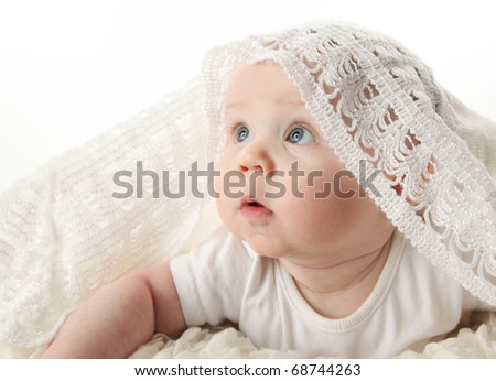 Portrait of an adorable baby with white blanket over head looking up toward light, isolated on white