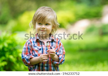 Portrait of an adorable child holding dandelion - stock photo